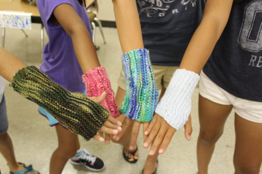 young girls showing off their finished knit mitts