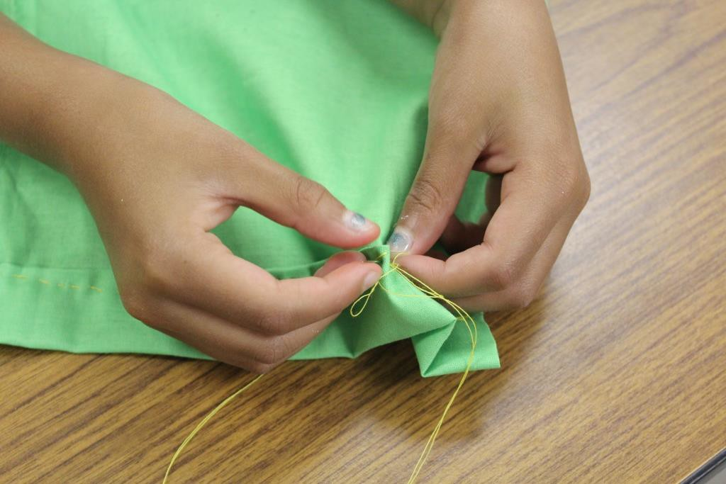 young child learning to sew
