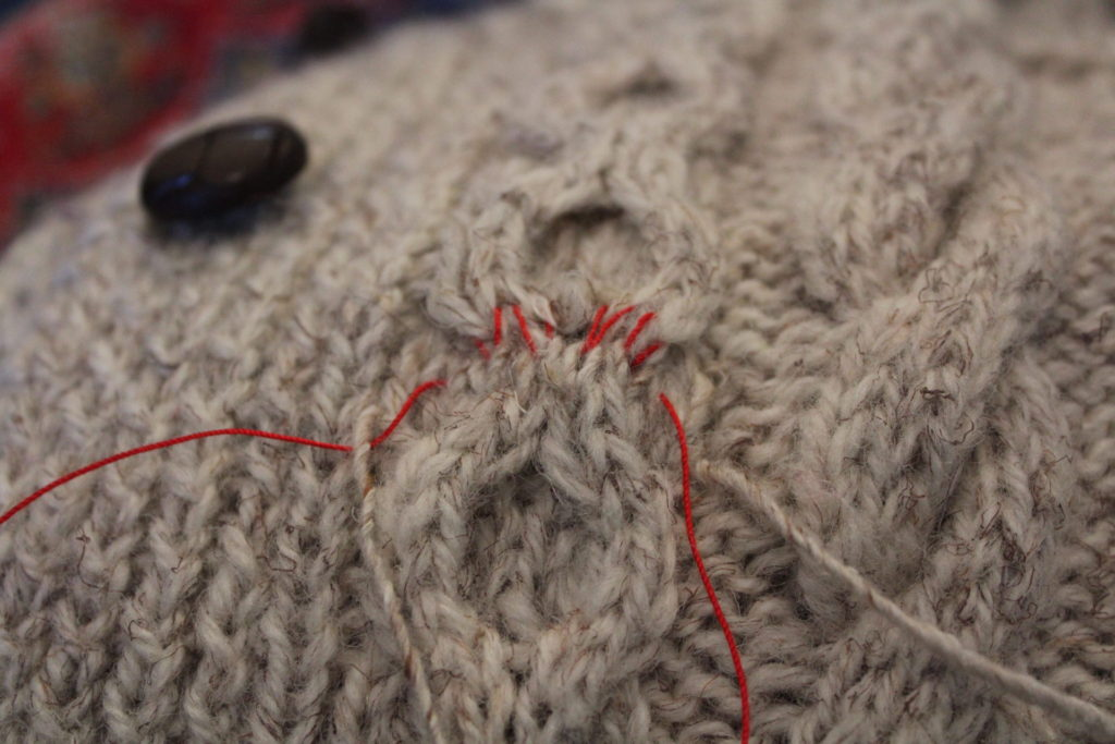 Sweater repair half done, only red guidelines remain.