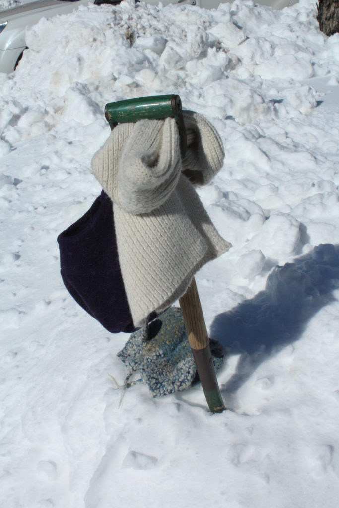 hat, mittens, gloves and scarf hanging from an unused shovel in a pile of snow.