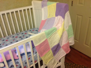 A crib with blankets waits for a new arrival